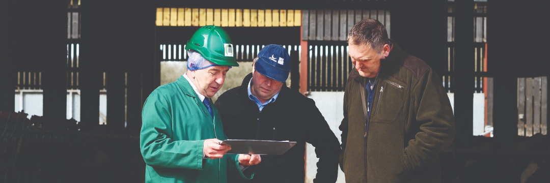 Three people looking at a clipboard on a farm